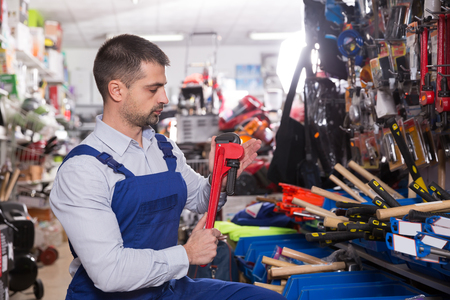 Man is choosing adjustable wrench in tools store 스톡 콘텐츠