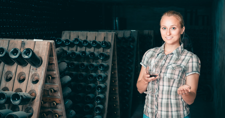 portrait of positive smiling young woman holding glass with wine sample in cellar with bottles
