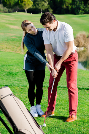 Golf trainer showing male player how to hit ball rightly
