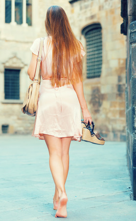 Young smiling woman walking in historic city center