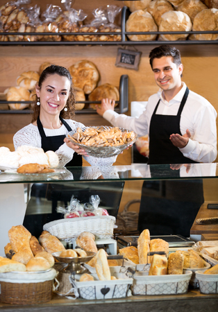 Cheerful young seller staff offering bread and different pastry for sale