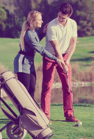 Happy golf trainer showing male player how to hit ball rightly