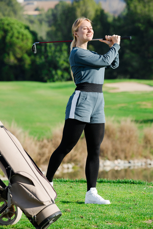 Female golf player is succeeded in ball hitting at golf course.