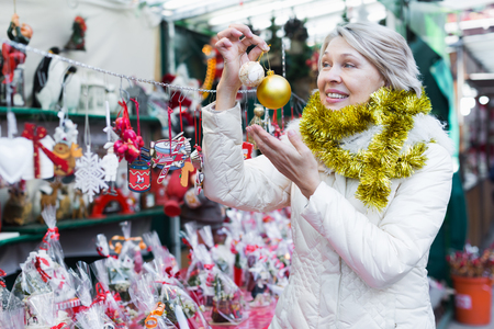 Portrait of happy mature woman in tinsel with Christmas toys at fair outdoor