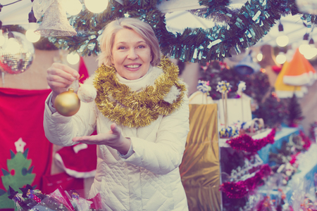 Smiling woman is buying toys for X-mas tree in the market outdoor.