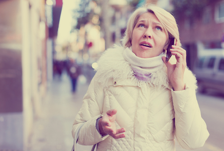Perplexed woman is talking by phone outdoor.