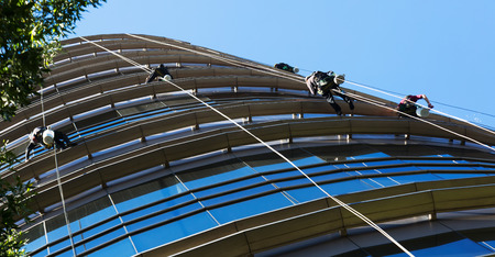 Group of industrial alpinists working on large windows of skyscraper Stock Photo
