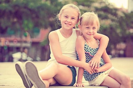 Two small happy sisters fun spending time together outdoors