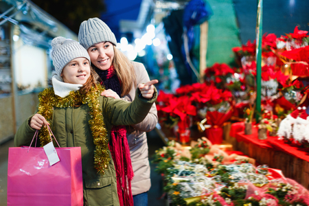 Young cheerful positive glad girl and her mother are buying Christmas ornamentals in the market outdoor. Фото со стока