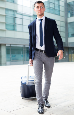 Successful businessman in suit with suitcase is staying near the building of airport. Stock Photo