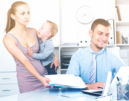 Adult male lawyer talking with young smiling woman with little son