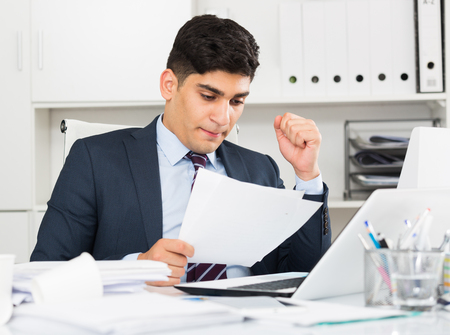 Adult office manager is reading documents about the transaction in office.