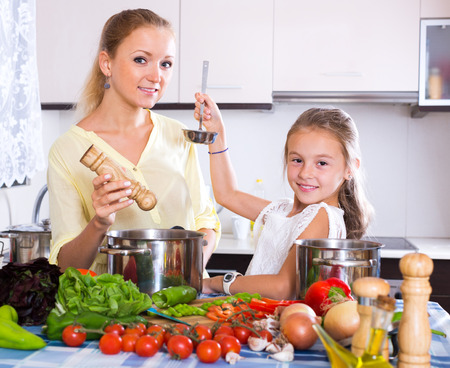 Happy young mother and little girl preparing vegetables in slow-cooker Banque d'images