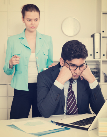 Young stressed businessman in office with dissatisfied female colleague behind Foto de archivo