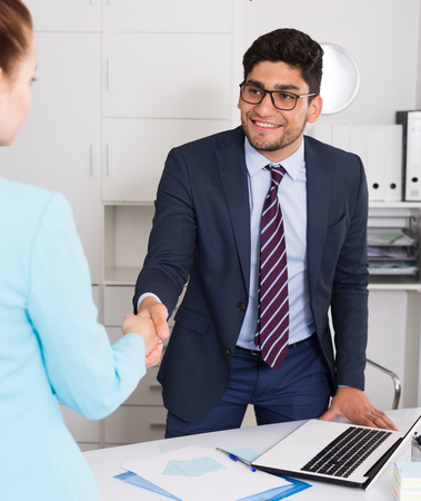 Young businessman meetings female colleague in office and shaking her hand Stock Photo