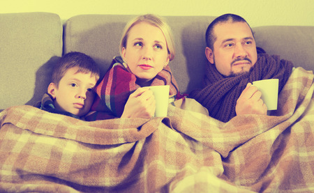 Ill family wrapping in blanket on couch at home drinking hot tea Reklamní fotografie