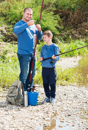 Smiling young man and little boy spending time outdoors and fishing
