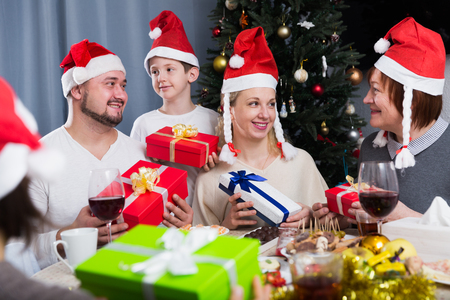 Three generations of happy family sitting around traditional holiday table with Christmas gifts Standard-Bild