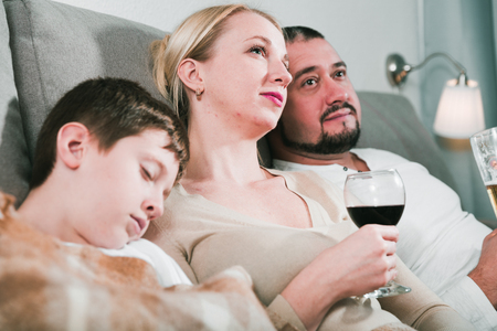 Loving spouses relaxing together on sofa near sleeping son Stock Photo