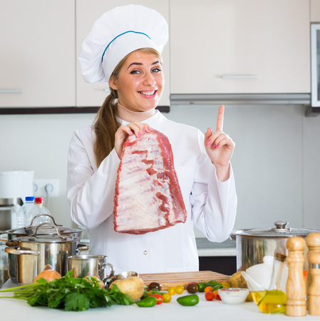 Young woman cooking meat for dinner in home interior  Stock Photo