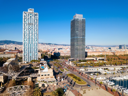 Modern cityscape of Barcelona with skyscrapers on embankment on sunny day