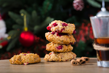 Stack of oatmeal biscuits with cranberry and cup of tea against backdrop of dressed Christmas tree
