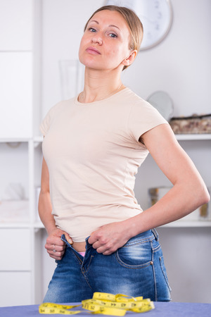 Woman making efforts to button up jeans because of excess weight