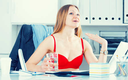 Attractive businesswoman in red bra cooling herself with glass of water