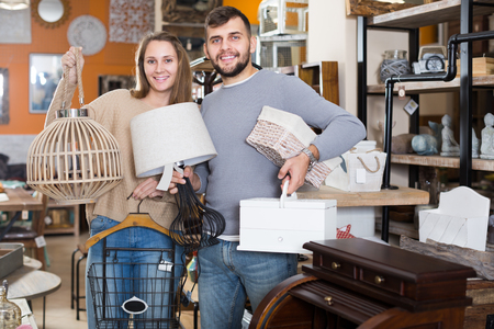 Portrait of happy young  customers standing with purchases in furnishings store