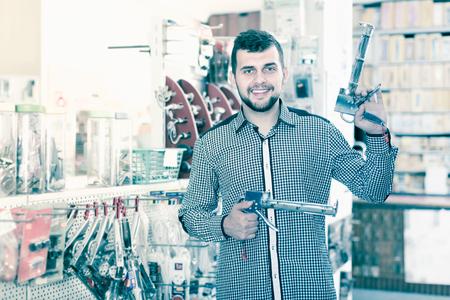cheerful male customer examining various glue guns in houseware store