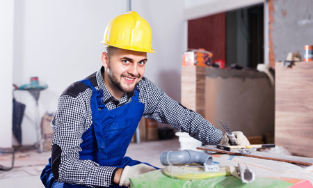 Diligent serious male worker is preparing for repair in the room at object