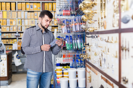man customer examining various glue tubes in houseware store Imagens - 96309075