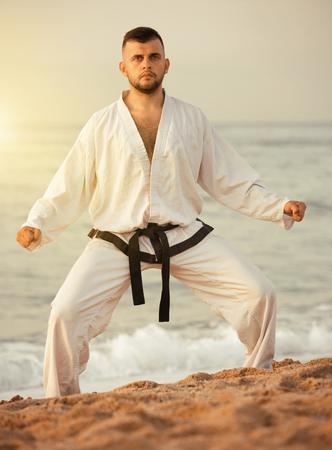 Cheerful male practising karate kata poses at seaside