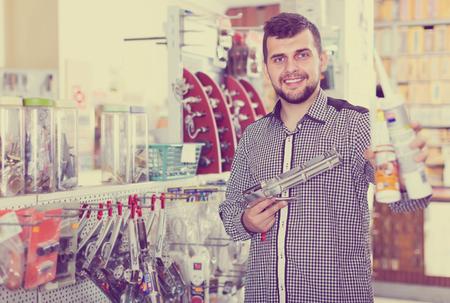 cheerful male customer examining various glue tubes in houseware store