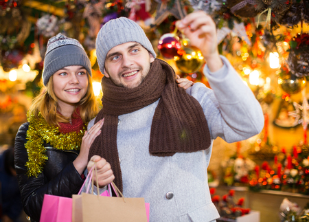 Portrait of joyful young couple with Christmas toys at fair outdoor Stock Photo