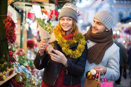 Portrait of joyful girl and boy choosing  toys and Christmas tree at fair