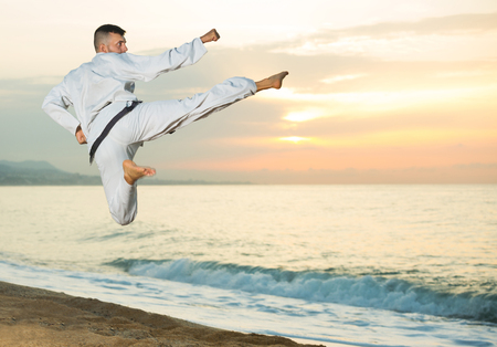 Positive sportive guy doing karate poses at  sunset sea shore