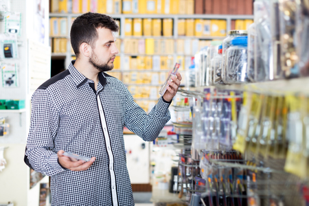 Smiling male customer examining various DIY details in houseware store Stock Photo