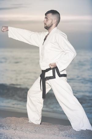 Man is training the Kokutsu-dachi stance on the beach near the sea.