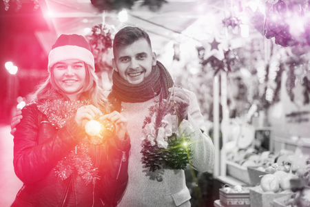 Portrait of joyful young couple in Christmas hat with Christmas purchases at fair Stock Photo