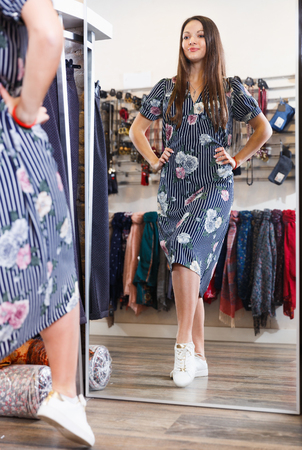Positive cute girl customer posing in new fashion dress at mirror in the  shop
