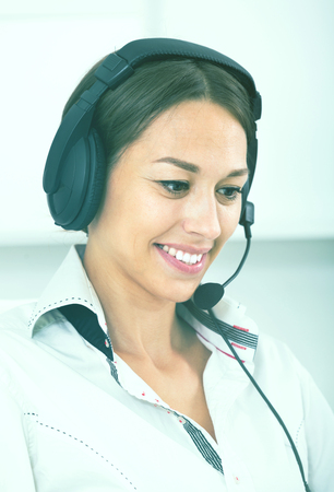 portrait of joyful woman with headset on answering at company office  Stock Photo