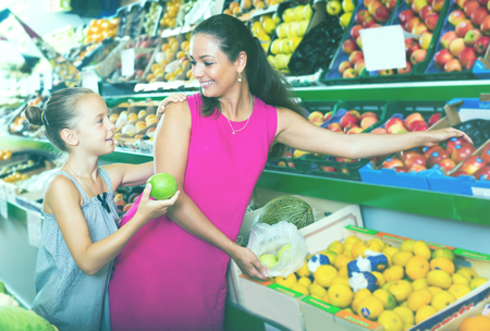 Cheerful female with daughter buying fresh apples in fruit section in grocery shop