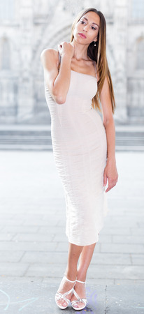 portrait of young cheeful british female in sexually ivory midi gown standing in town Stock Photo