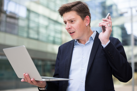 Cheerful businessman with notebook talking about work on the mobile phone at the street Stock Photo