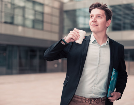 Professional man in jacket walking with coffee and document folder Stock Photo