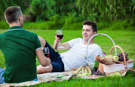 Happy cheerful positive smiling man enjoying life on picnic outdoors with his friend