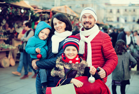 Happy parents with children customer near counter with Christmas decoration Stock Photo