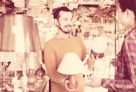 Young english man and girl in lighter shop choosing stylish and modern lamp for house interior Stock Photo