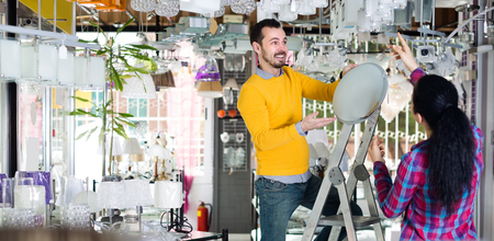 Male and female in lighter shop are choosing stylish round matt glass ceiling lamp.
